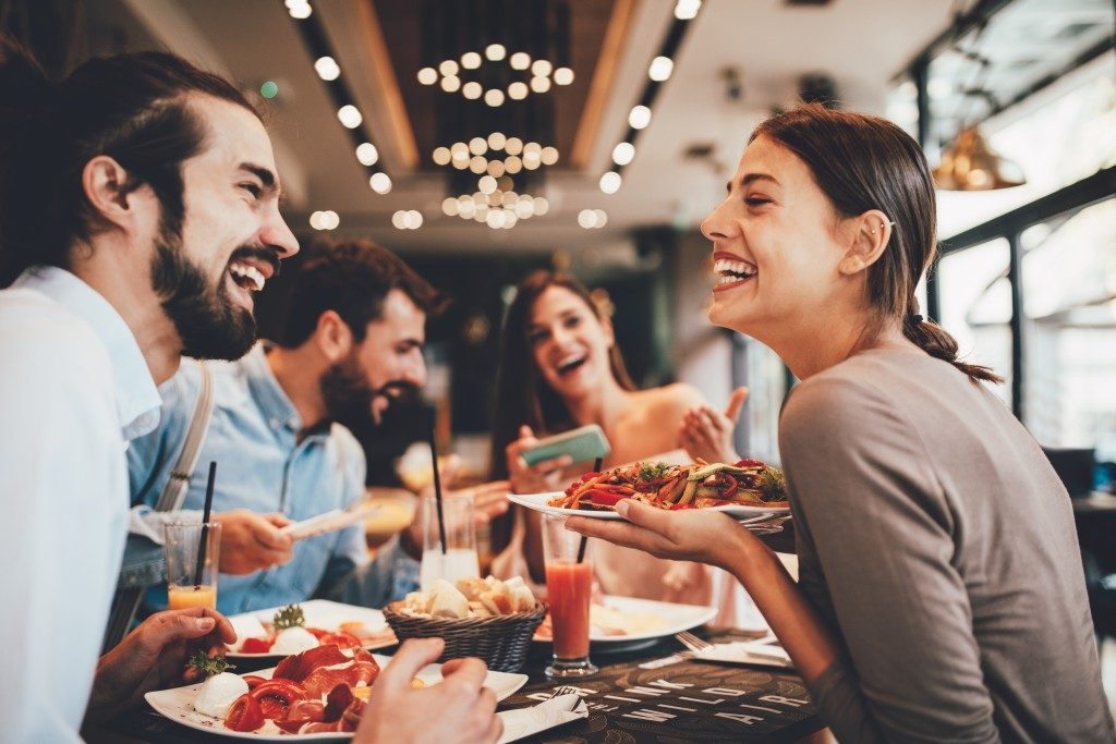Group of people eating happily at a restaurant