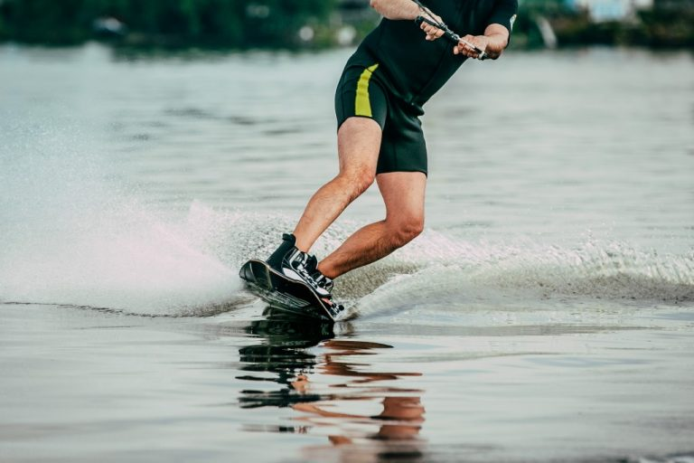 male athlete rides on a wakeboard on lake in summer